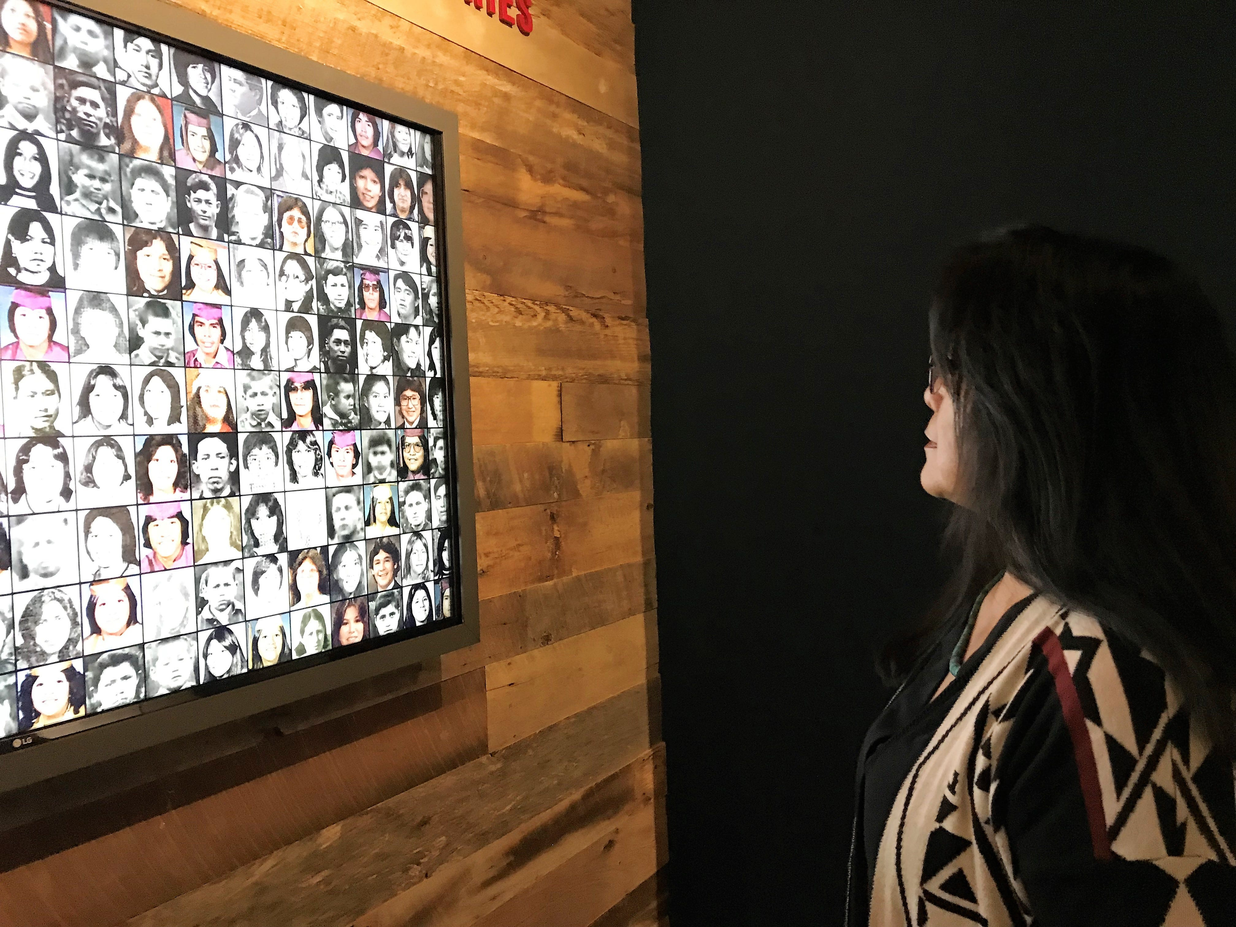 """Patty Talahongva looks at the photos of students who went to Native boarding schools. The photos are part of the Heard Museum's """"Away From Home: American Indian Boarding School Stories"""" exhibit."""