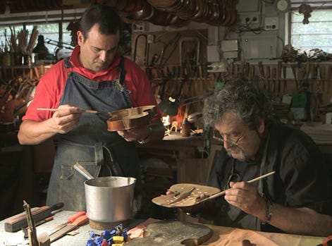 Israeli violinmaker Amnon Weinstein restoring a violin in his workshop with his son.