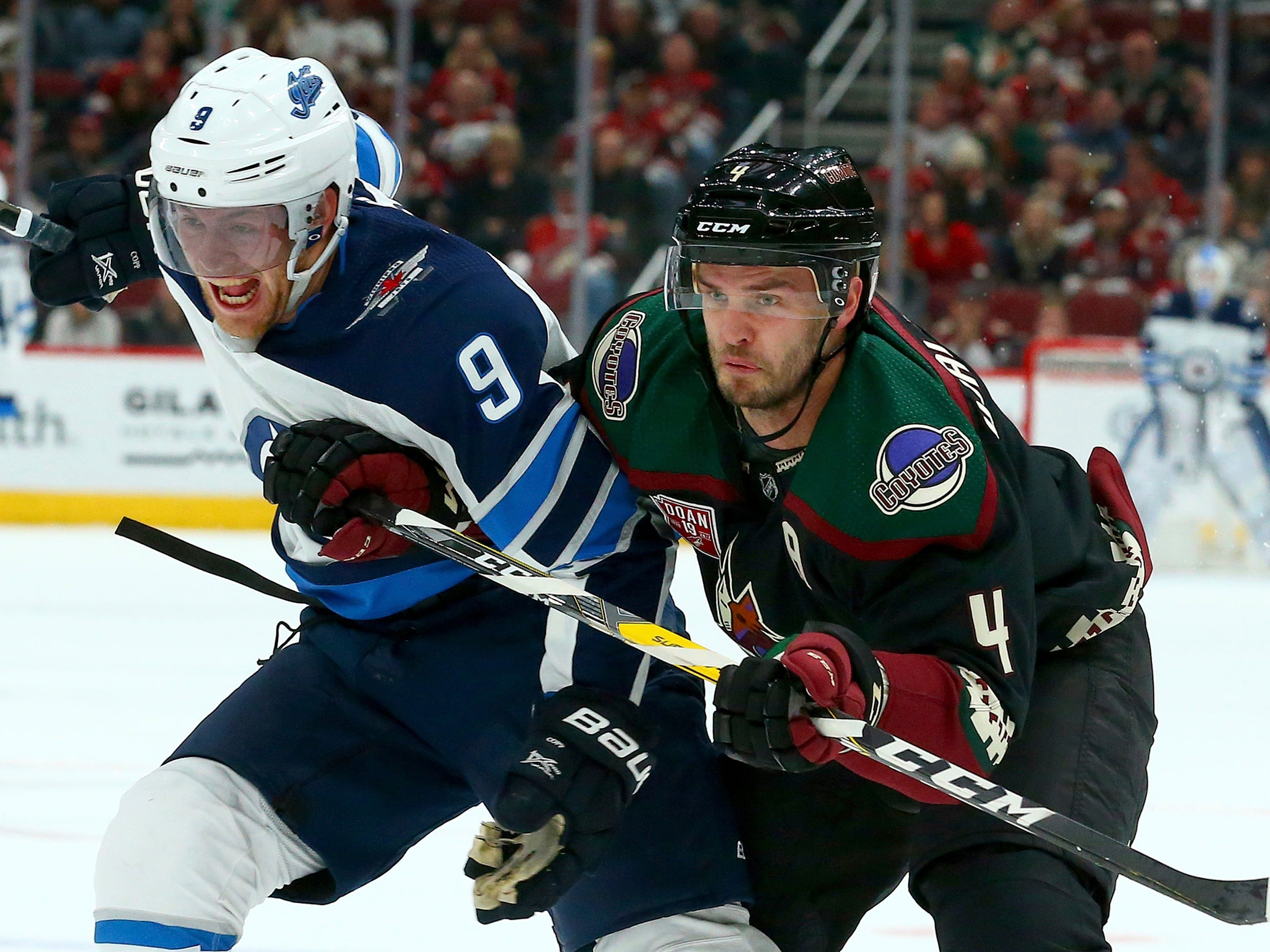 Arizona Coyotes defenseman Niklas Hjalmarsson (4) and Winnipeg Jets center Andrew Copp (9) tangles with one another during the first period of an NHL hockey game Sunday, Feb. 24, 2019, in Glendale, Ariz.