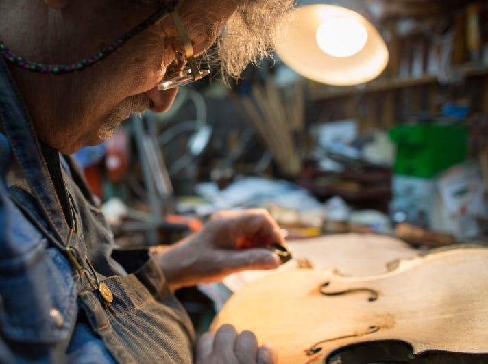 Israeli violinmaker Amnon Weinstein working on a violin in his workshop.