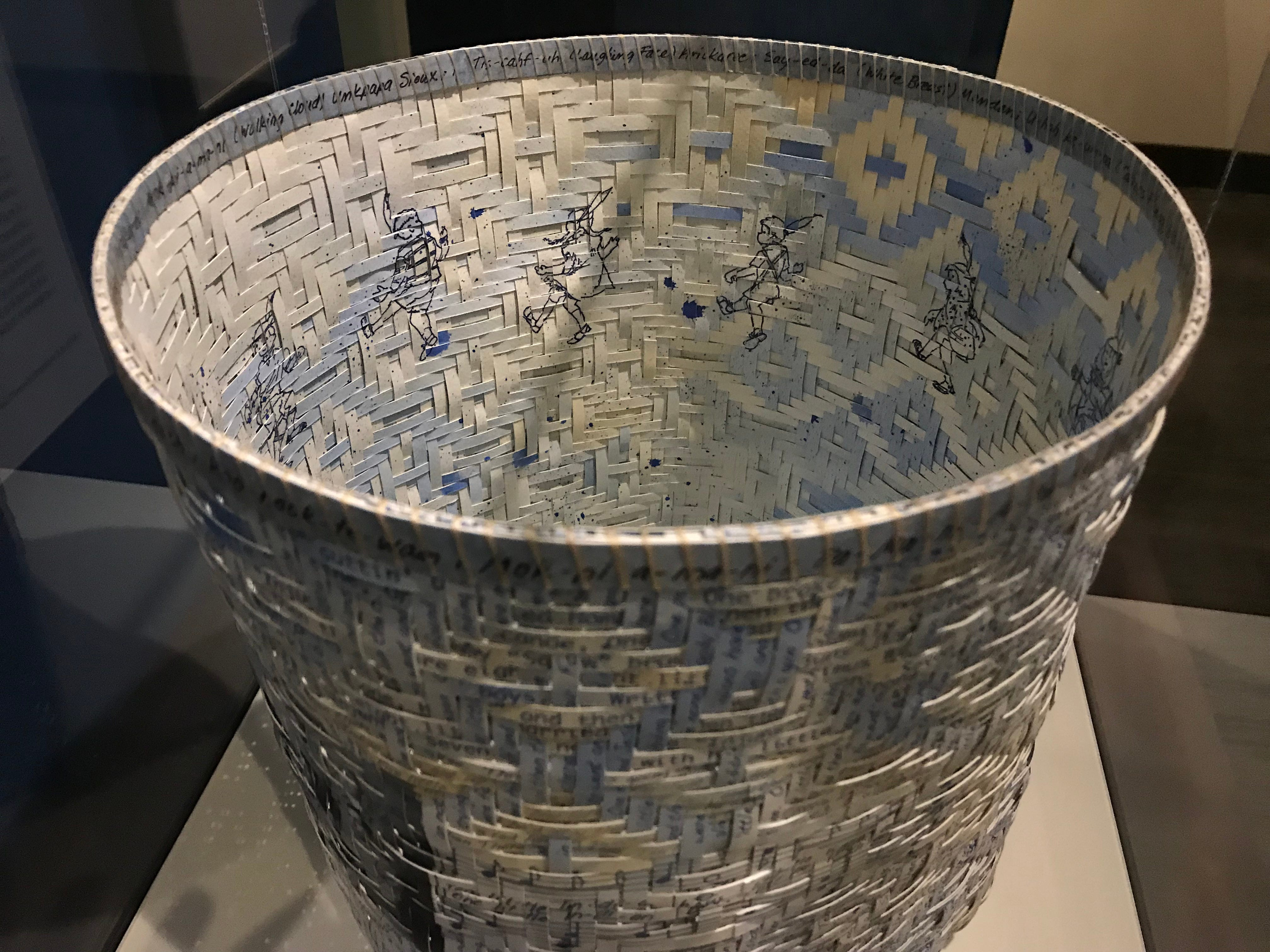 """Inside the A single-weave basket by Artist Shan Goshorn titled """"10 Little Indians,"""" kids can be seen dancing around. The basket is part of the  """"Away From Home: American Indian Boarding School Stories"""" exhibit at the Heard Museum."""