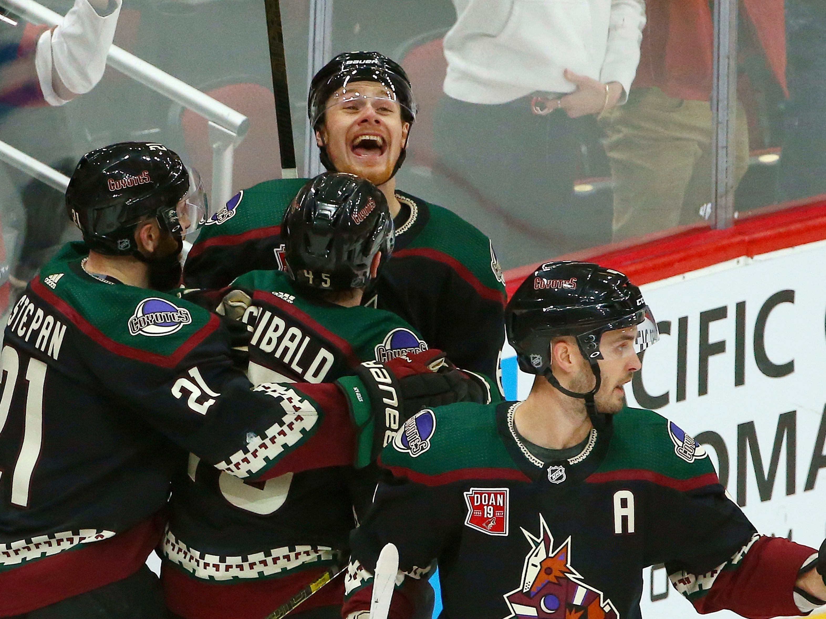 Arizona Coyotes left wing Lawson Crouse, top, shouts as he celebrates his goal against the Winnipeg Jets with Coyotes center Derek Stepan (21), right wing Josh Archibald, second from left, and defenseman Niklas Hjalmarsson, right, during the second period of an NHL hockey game Sunday, Feb. 24, 2019, in Glendale, Ariz.