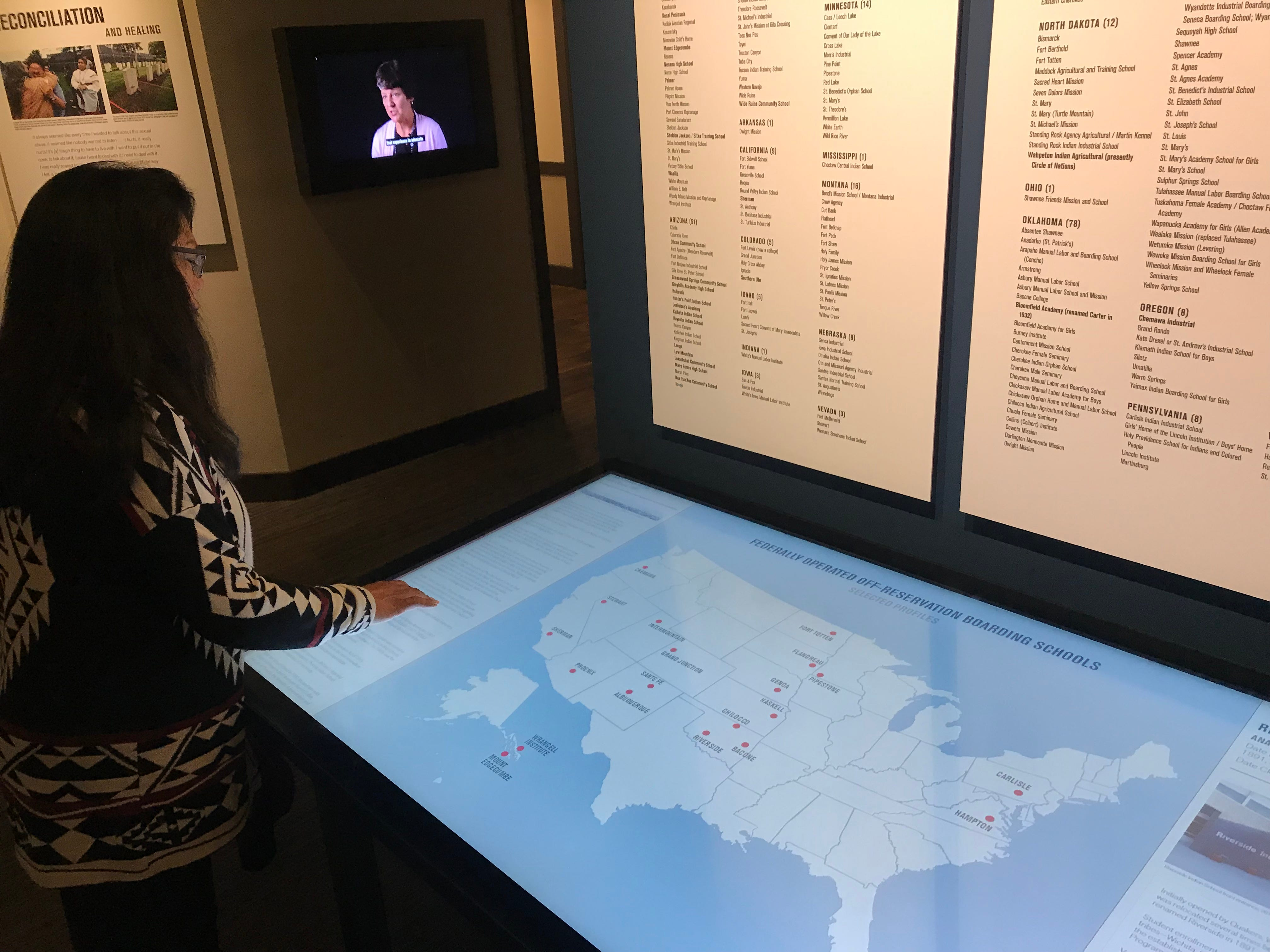 """Patty Talahongva browses through the interactive map that shows Native boarding schools still open today. The map is part of the the Heard Museum's """"Away From Home: American Indian Boarding School Stories"""" exhibit."""