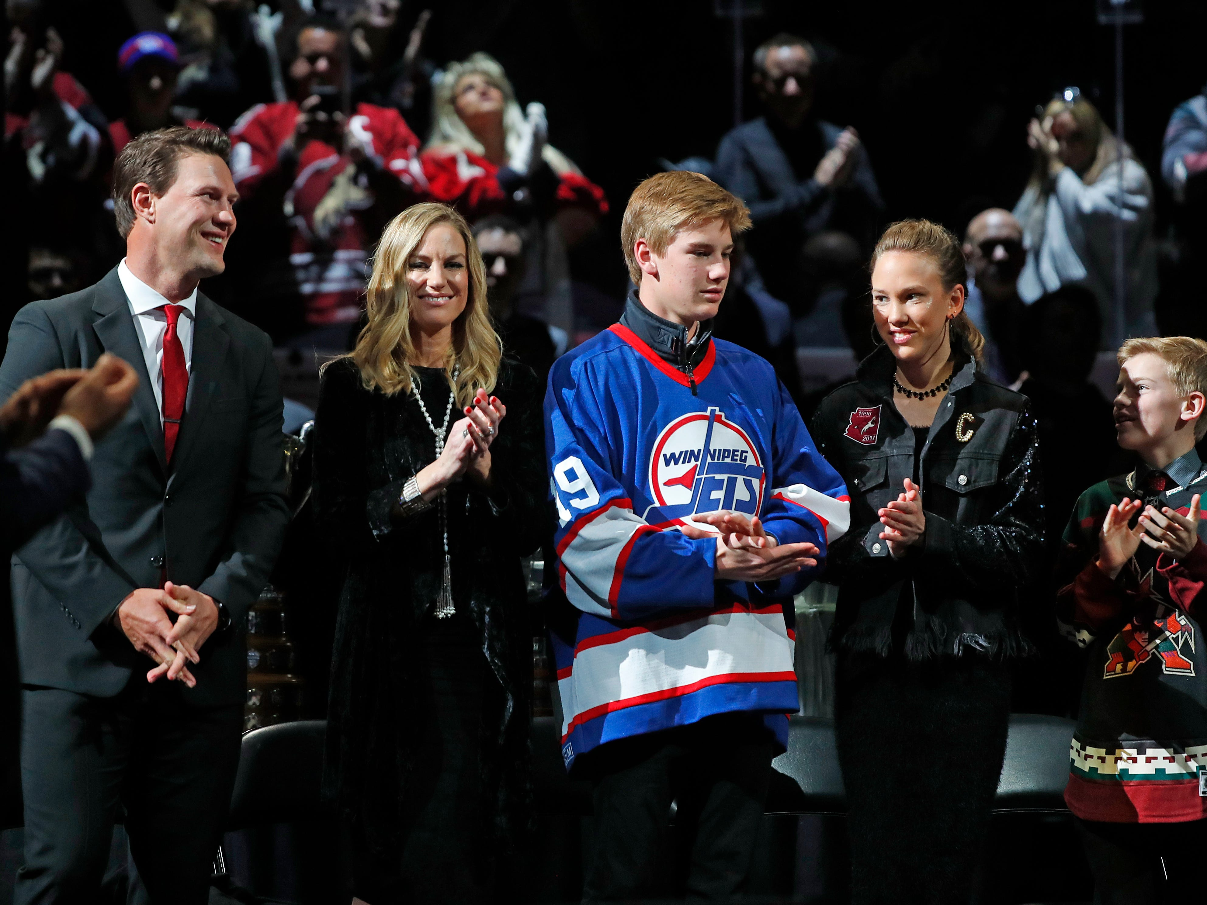Shane Doan smiles as he receives a standing ovation next to his wife Andrea and children Josh, Karys and Carson during his jersey retirement ceremony at Gila River Arena in Glendale, Ariz. on February 24, 2019.