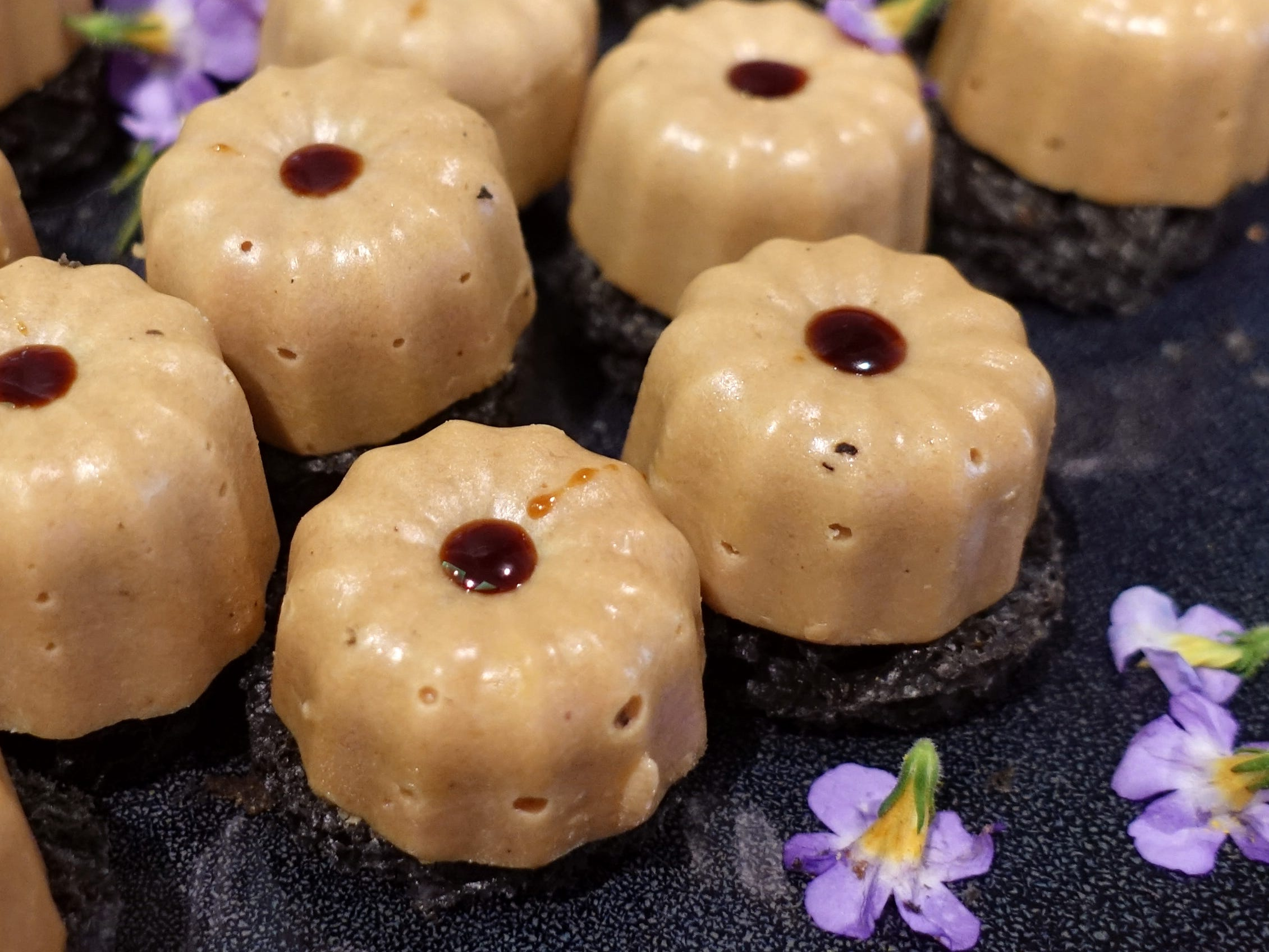 Canneles of foie gras with black brioche from Geordie's Restaurant at the Wrigley Mansion at the 2019 Devour Culinary Classic at the Desert Botanical Garden in Phoenix.