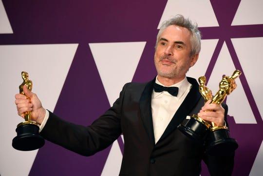 El director de Roma, Alfonso Cuarón, posa con sus tres estatuillas Oscar.