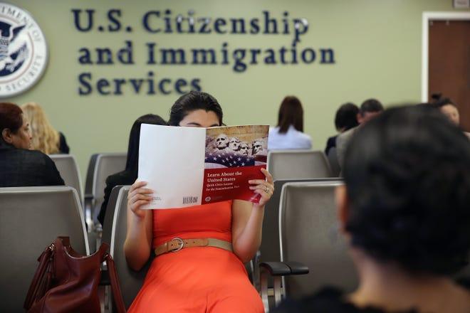 Una mujer lee su manual de ciudadanía antes de entrar a la entrevista.