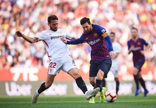 Lionel Messi elude la marca de un defensor del Sevilla.