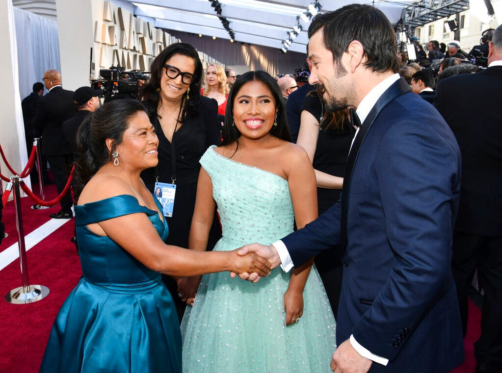 Margarita Martinez Merino, left, shakes hands with Diego Luna, right, as Yalitza Aparicio looks on during arrivals at the Oscars on Sunday, Feb. 24, 2019, at the Dolby Theatre in Los Angeles. (Photo by Charles Sykes/Invision/AP)