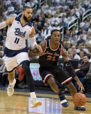 Fresno State guard Deshon Taylor (21) drives past Nevada forward Cody Martin (11) in the first half of an NCAA college basketball game in Reno on Saturday.