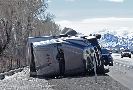 An unidentified man uses a rolled over high profile vehicles to shield himself from the wind on the 580 next Washoe Lake on Monday Feb 25, 2019. High wind are expected through the day.