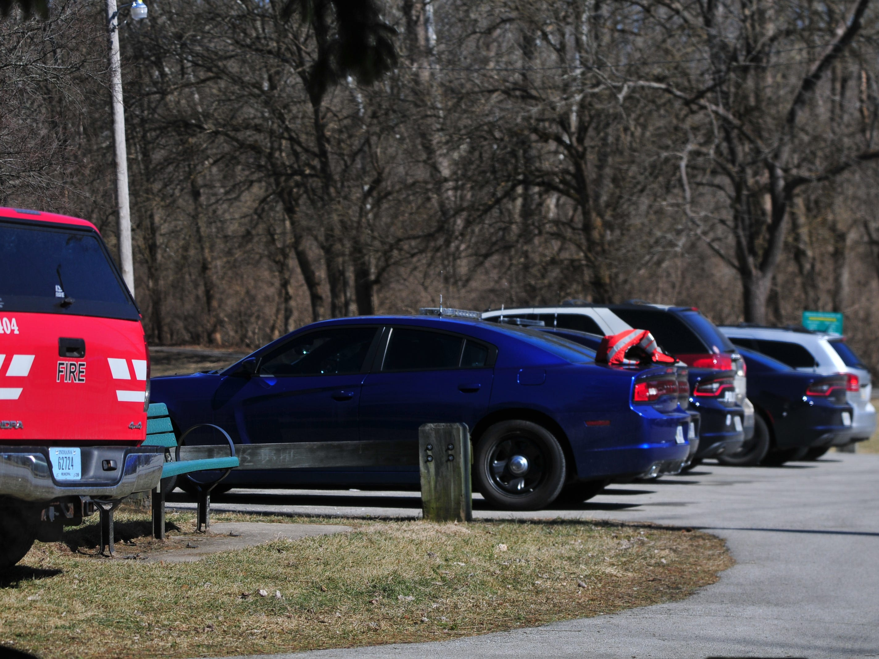 Police and fire vehicles are parked at the Test Road trail head Monday morning during the search for Jake Huntington.