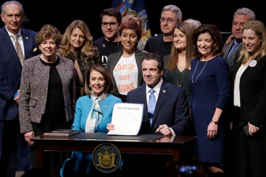 "House Speaker Nancy Pelosi, center left, joins New York Governor Andrew Cuomo, center right, as they pose for a picture after signing a gun control bill at a ceremony in New York, Monday, Feb. 25, 2019. Cuomo signed a ""red flag"" bill, which attempts to prevent people who present a threat to themselves or others from purchasing or owning a gun."