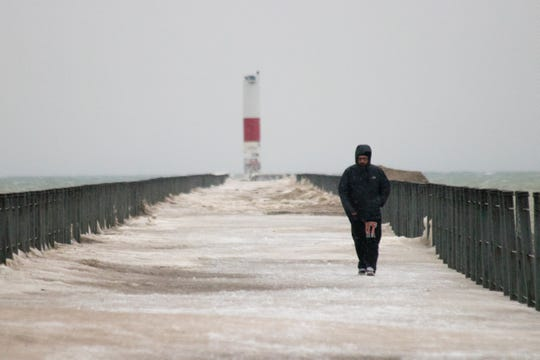 Peter Griffin of Gates walks the Charlotte Pier at Ontario Beach Park during the high wind warning on Feb. 24, 2019.
