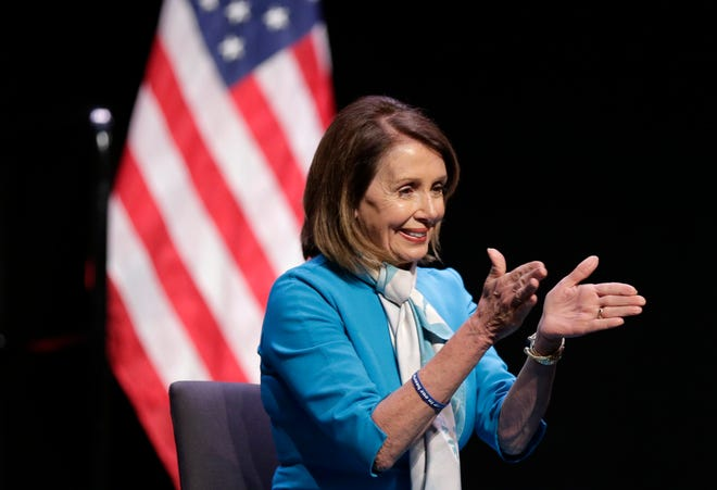 """House Speaker Nancy Pelosi claps while New York Governor Andrew Cuomo speaks during a bill signing ceremony in New York, Monday, Feb. 25, 2019. Pelosi joined Cuomo as he signed a """"red flag"""" bill, which attempts to prevent people who present a threat to themselves or others from purchasing or owning a gun. (AP Photo/Seth Wenig)"""