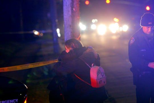 Dos mujeres se abrazan en la esquina de E. Laurel Drive y Granada Avenue cerca del lugar donde ocurrió un fatal tiroteo el 22 de febrero de 2019.
