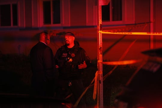 A Salinas police officer speaks with a man at the corner of E. Laurel Drive and Granada Avenue near a deadly shooting Friday night.