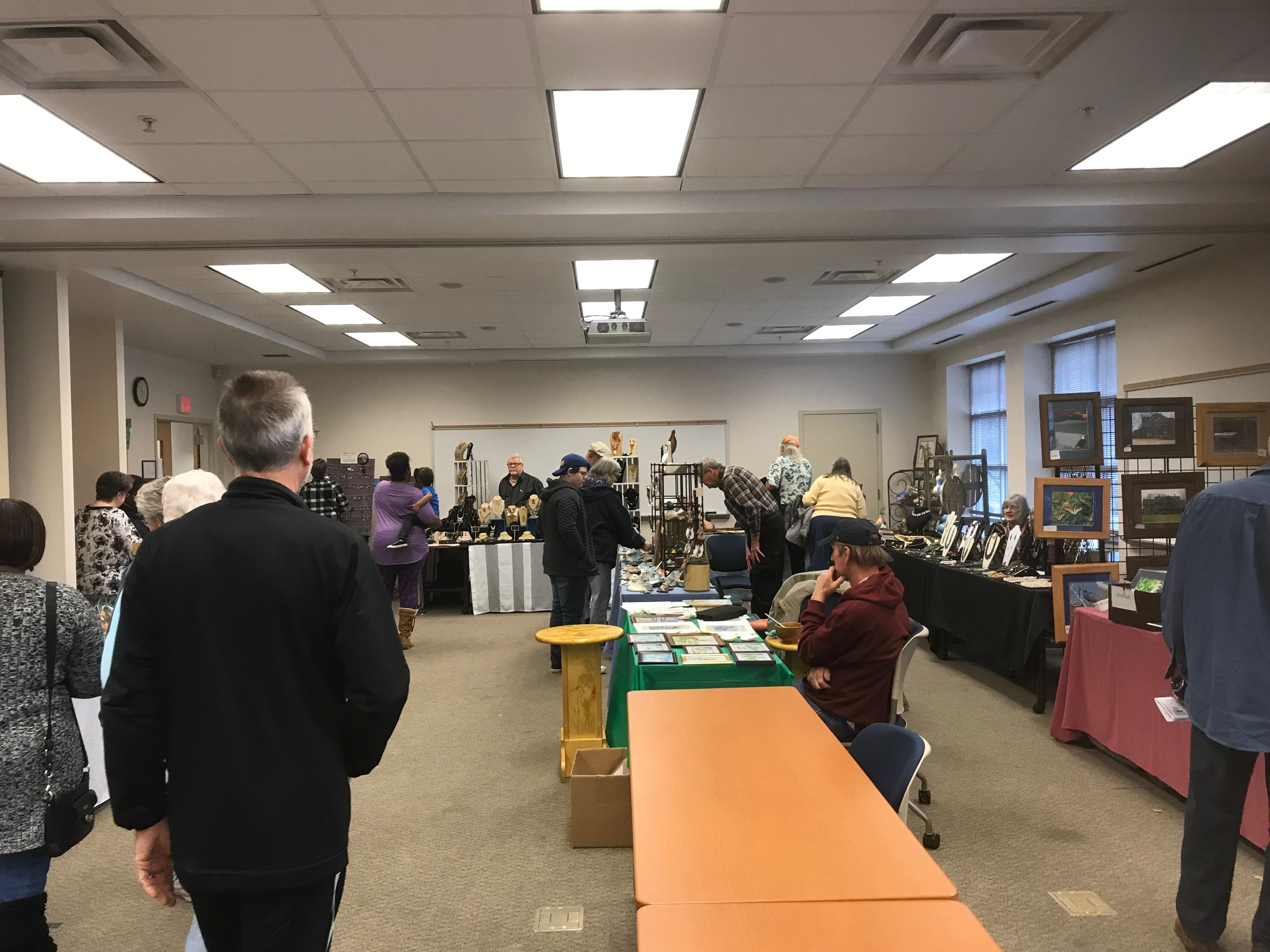 Attendees look at the work of artists and craftspeople at Eastern Shore Community College's Heritage Festival on Saturday, Feb. 23, 2019.