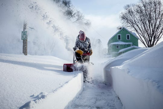 Michael Mueller snow blows the sidewalk near his house Sunday, Feb. 24, 2019, in Rochester, Minn., after heavy snow overnight. ( Joe Ahlquist/The Rochester Post-Bulletin via AP)