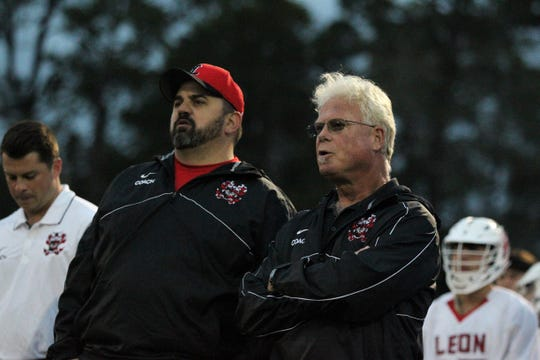 Allan Rice (right) came out of coaching retirement to return as Leon's head lacrosse coach. He and assistant coach Chuck Ringel watch as the Lions' lacrosse team play Ocala Forest in its season opener on Feb. 18, 2019.