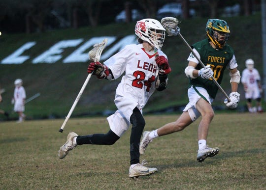 Leon's Spencer Jenkins carries upfield as the Lions' lacrosse team played Ocala Forest in its season opener on Feb. 18, 2019.