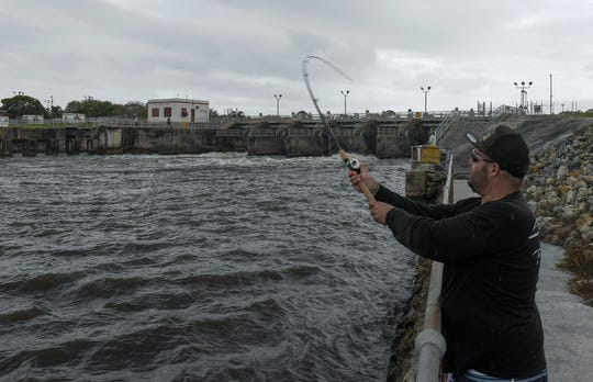 "Ed Metz, of Jensen Beach, tries his luck fishing off the northeast wall of the St. Lucie Lock and Dam as water from the C-44 canal flows through two of the locks downstream towards the St. Lucie River on Monday, Feb. 25, 2019, in Martin County.  ""The [water] release helps, it brings the Snook in, they gobble up the bait,"" Metz said about the benefits of the release for fishing, but not so much for the river. ""Not good, [it] makes the river dirty."""