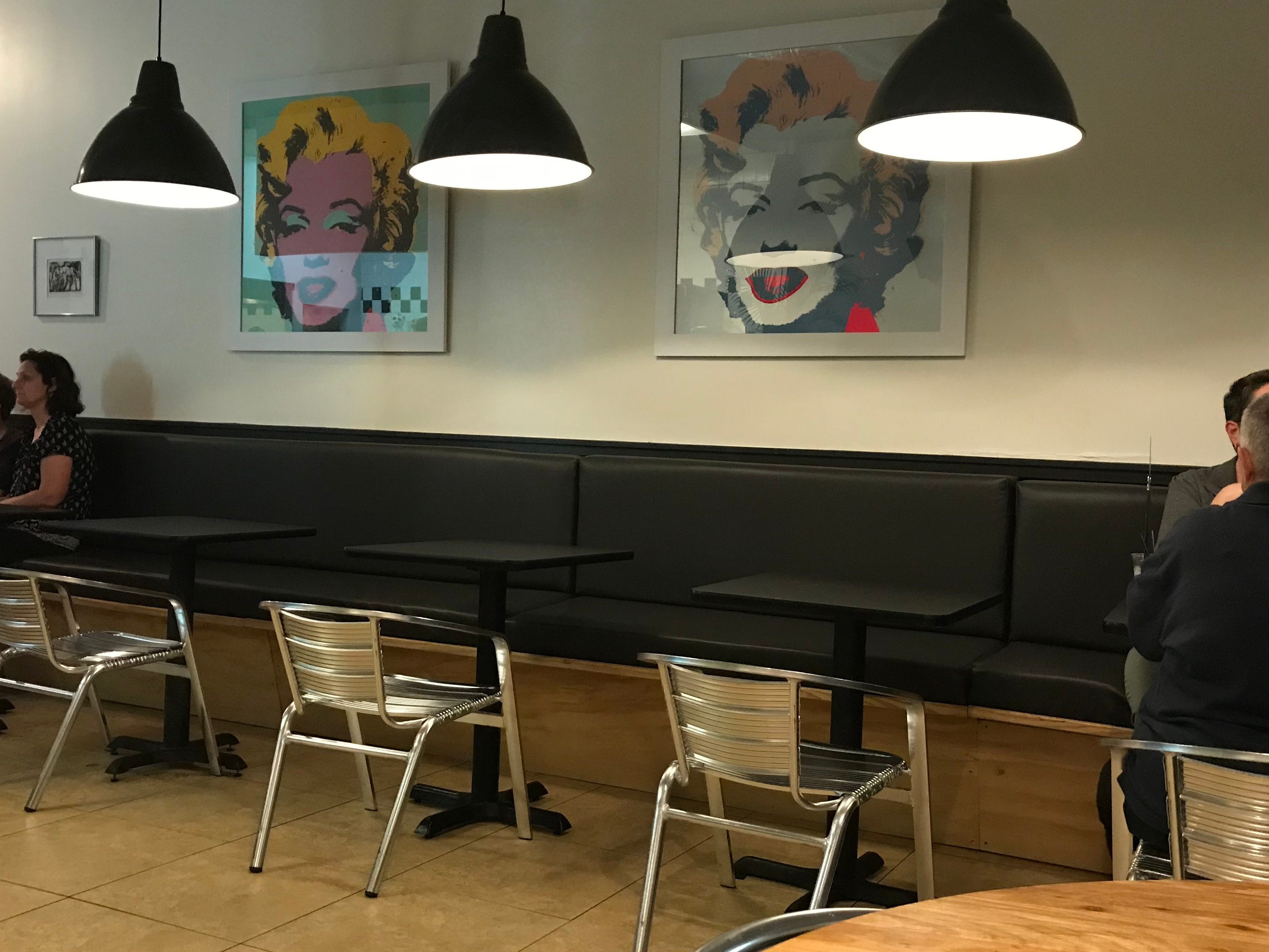 There is a banquette lining one wall with colorful posters of Andy Warhol's Marilyn Monroe above.