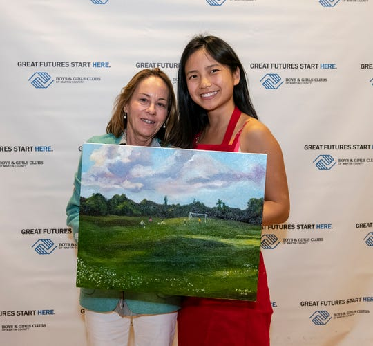 Heidi Cox, left, bought the painting created by Coleen Chan, right, an alumna of the Cole-Clark Club in Hobe Sound for $2,500 at the Great Futures Dinner of the Boys & Girls Clubs of Martin County.