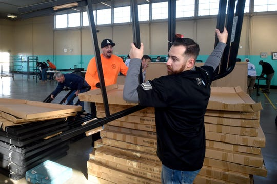 Scott Zimmerman, of Local 805 Southwest Regional Council of Carpenters, unboxes bedframes as he and dozens of volunteers assembled 100 beds at the Regional Homeless Shelter in Oxnard on Monday. The beds were paid for largely through donations from area cannibus dispensaries.  t the west county regional homeless shelter in Oxnard on Monday. Dozens of volunteers from the Local 805 Southwest Regional Council of Carpenters helped unload and assemble 100 beds paid for largely through donations from area cannabis dispensaries.