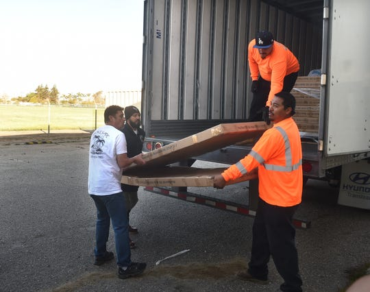 James Henschel, from left, of Tradecraft Farms dispensary, helps Omar Vieyra, Bronson Ross and Roberto Villegas, of Local 805 Southwest Regional Council of Carpenters, unload 100 beds at the west county regional homeless shelter in Oxnard Monday. The beds were paid for in large part by Port Hueneme cannabis businesses.
