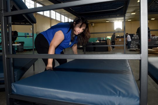 Francine Castanon, who serves on Oxnard's commission on homelessness, places a mattress on a newly assembled bed at the west county regional homeless shelter in Oxnard on Monday. Dozens of volunteers from the Local 805 Southwest Regional Council of Carpenters helped unload and assemble 100 beds paid for largely through donations from area cannabis dispensaries.
