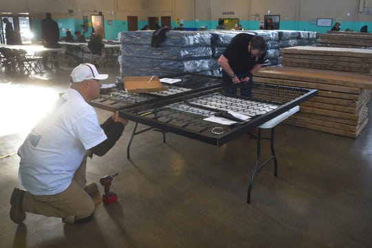 Cisco Carreno, left, and Manley McNinch, of Local 805 Southwest Regional Council of Carpenters, joined dozens of union members to assemble 100 beds at the west county regional homeless shelter in Oxnard on Monday. The beds were paid for largely through donations from area cannabis dispensaries.
