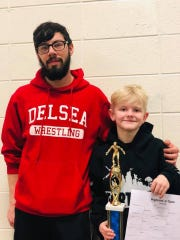 Chase Martino (right), 10, poses with his first-place trophy along with coach Steven Jillard.
