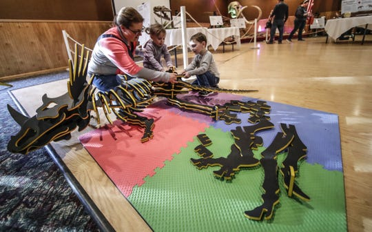 Stacy Packard assists her 2-year-old daughter Makenzie, and 3-year-old son Owen, to put back dinosaur skeletons made out of soft foam during the Colossal Fossils central Wisconsin exhibit Friday, Feb. 22, 2019, at North Star Lanes in Antigo, Wis. T'xer Zhon Kha/USA TODAY NETWORK-Wisconsin