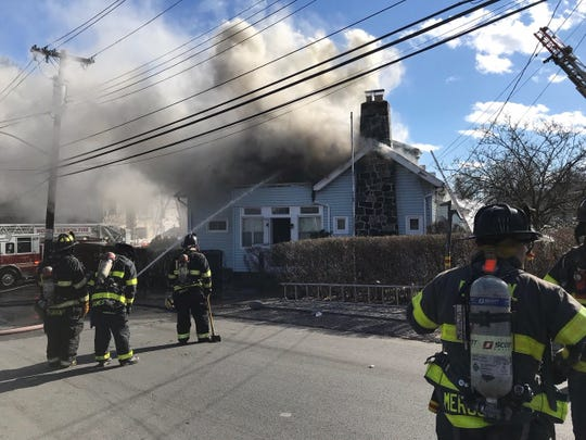 Firefighters battle a smoky, wind-blown fire at 5 Johnson St. in Mount Vernon, Monday, Feb. 25, 2019.