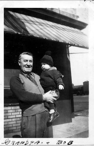 Bob, being held by his grandfather, Charles Holstein.