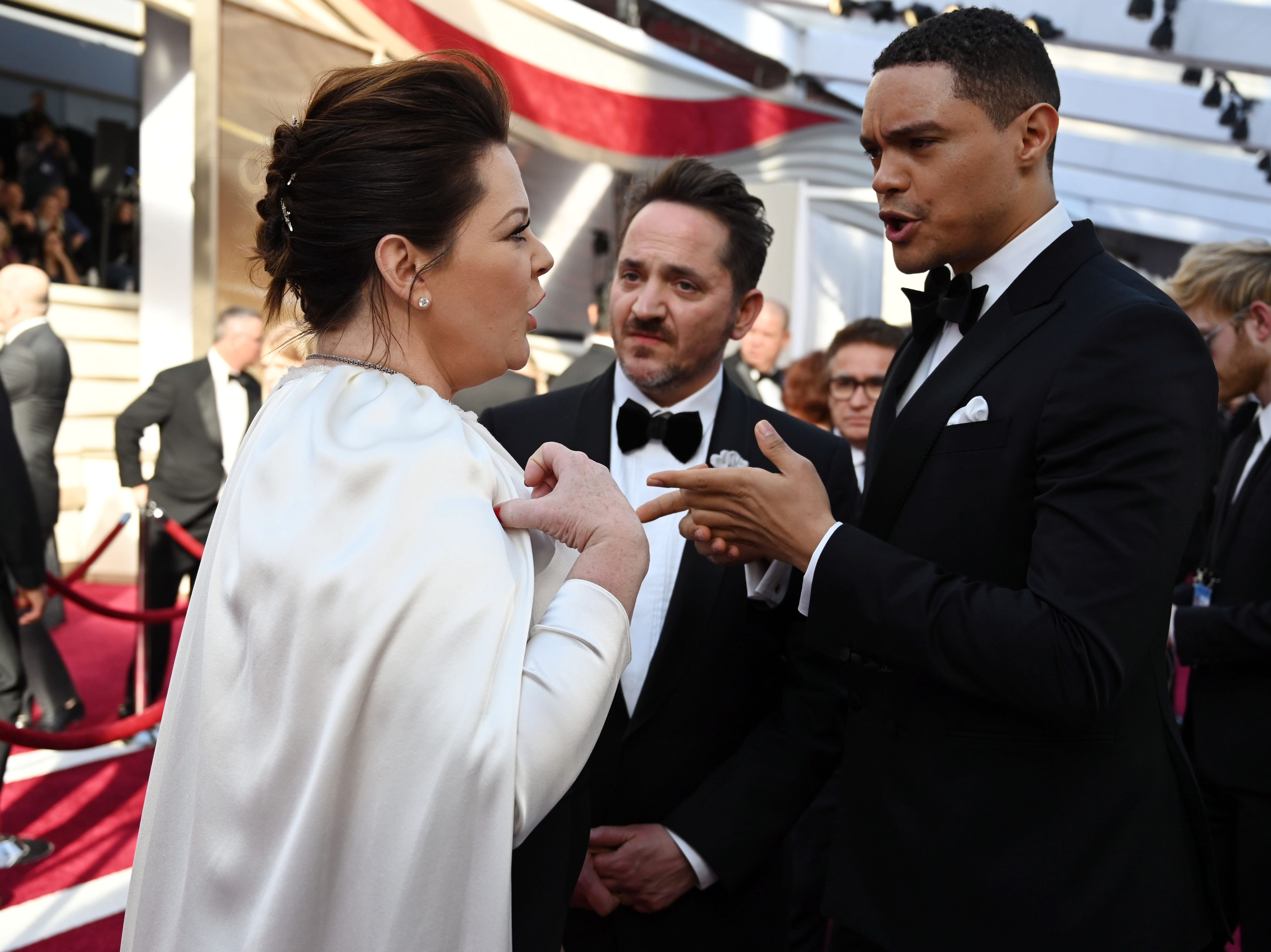 February 24, 2019; Los Angeles, CA, USA; Trevor Noah (r)  talks with Melissa McCarthy and her husband Ben Falcone as they arrive at the 91st Academy Awards at the Dolby Theatre. Mandatory Credit: Robert Hanashiro-USA TODAY NETWORK (Via OlyDrop)