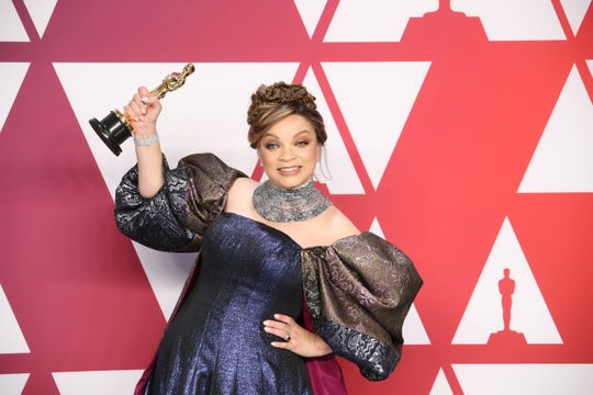 "Ruth E. Carter poses with the award for best costume design for ""Black Panther."""
