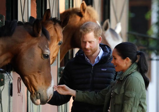 Prince Harry and Duchess Meghan stop to stroke horses in their stables during a visit to the Moroccan Royal Federation of Equestrian Sports in Rabat in Morocco, Feb. 25, 2019.