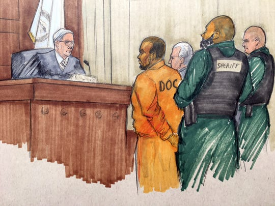 In this courtroom sketch, singer R. Kelly stands before Cook County Associate Judge Lawrence Flood during his arraignment Monday. Flood will be presiding over his case from this point on.