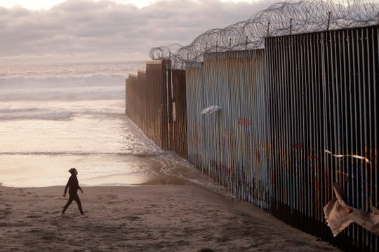 A woman walks on the beach next to a border barrier in Tijuana, Mexico Jan. 9, 2019. President Donald Trump has declared a national emergency to secure billions of dollars to build more barrier along the U.S.-Mexico border and Democrats are trying to halt the declaration.
