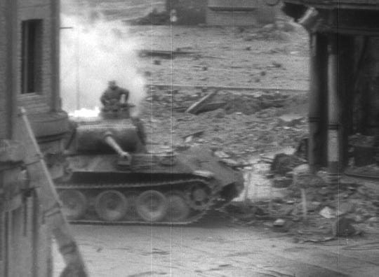A frame from a film sequence shows German tank crew members escaping their burning Panther tank after it was hit by fire from Clarence Smoyer's Pershing tank in Cologne, Germany.