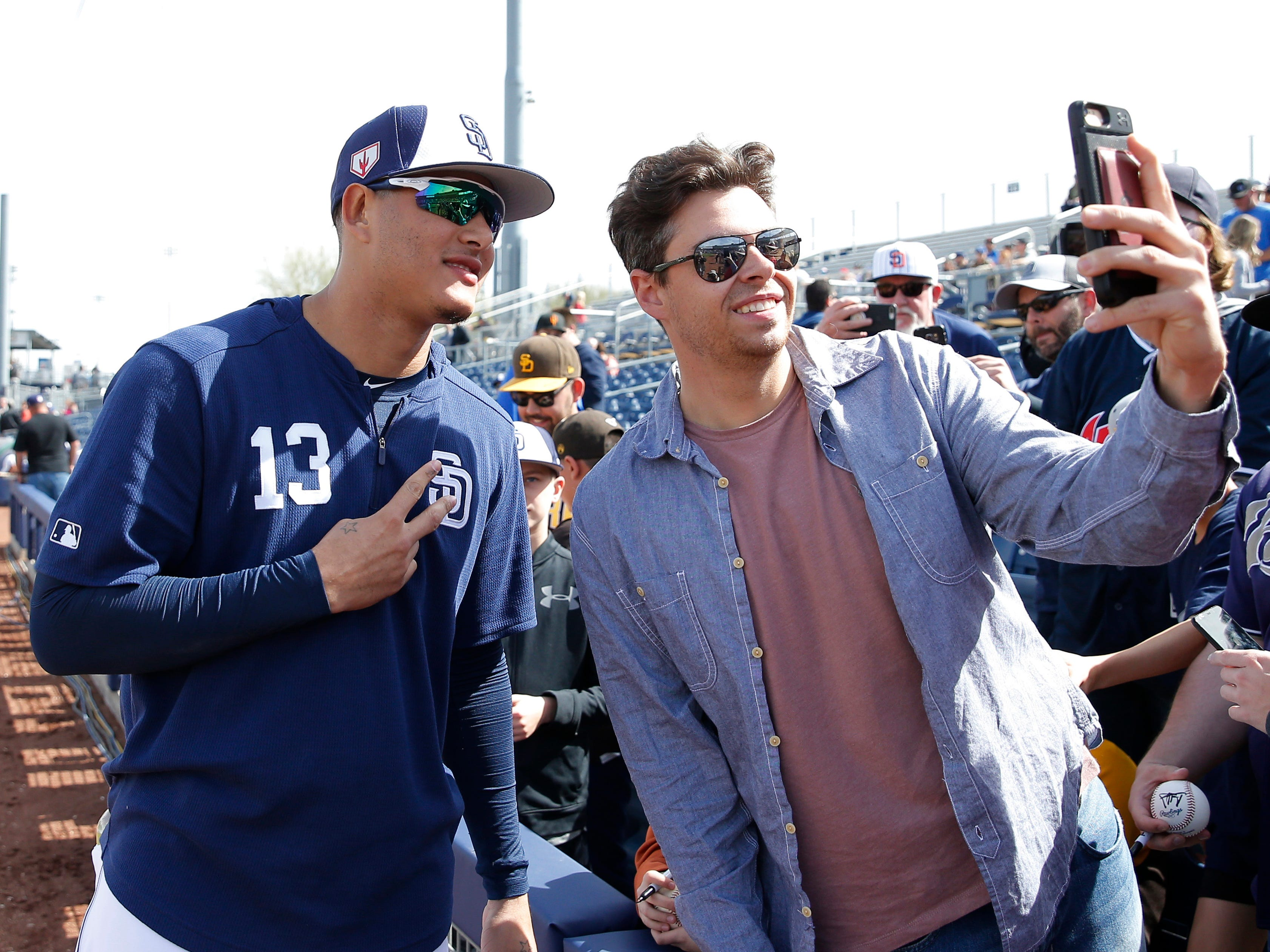 Feb. 24: New San Diego Padres third baseman Manny Machado takes pictures with fans before a spring training game against the Chicago White Sox at Peoria Stadium.