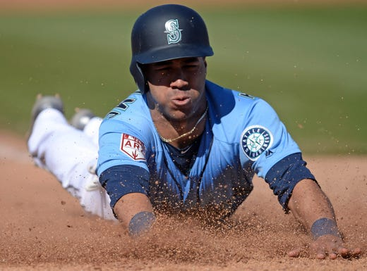 Feb. 23: Seattle Mariners center fielder Dom Thompson-Williams slides into home to score a run against the San Diego Padres at Peoria Stadium.