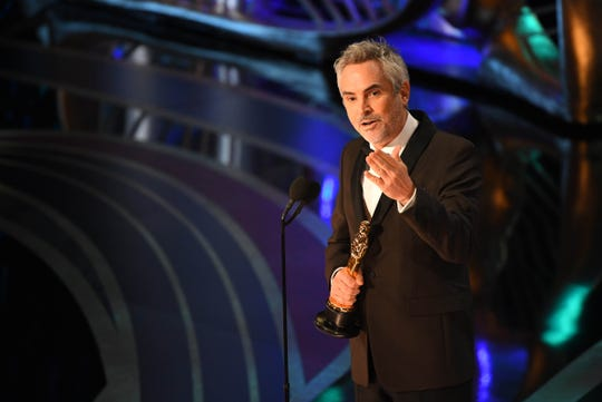 """Alfonso Cuaron accepts the award for achievement in cinematography for """"Roma."""""""