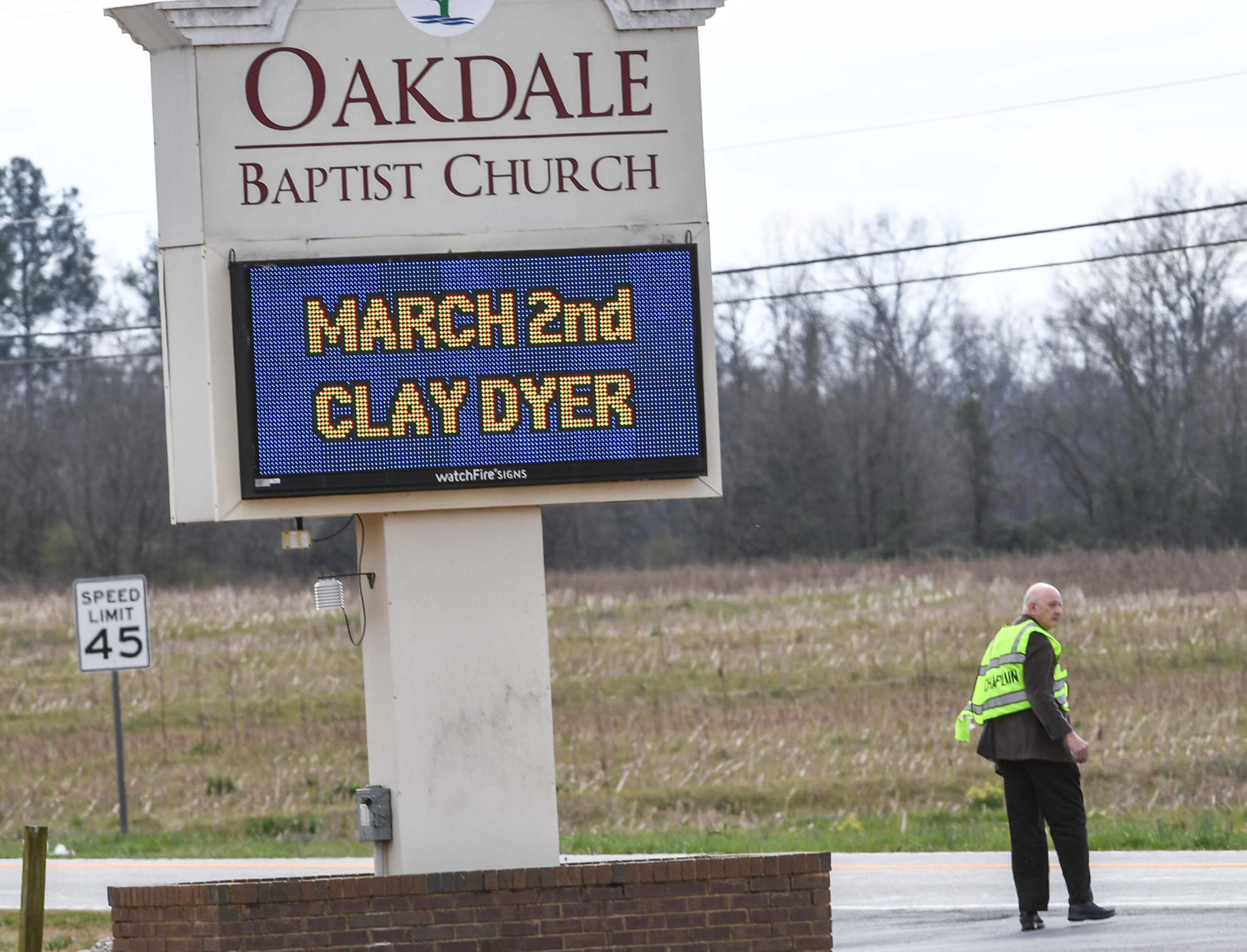 A man with a chaplain vest helps direct traffic at the scene of a three-car accident on state highway 24 just below Townville in front of Oakdale Baptist Church Tuesday.