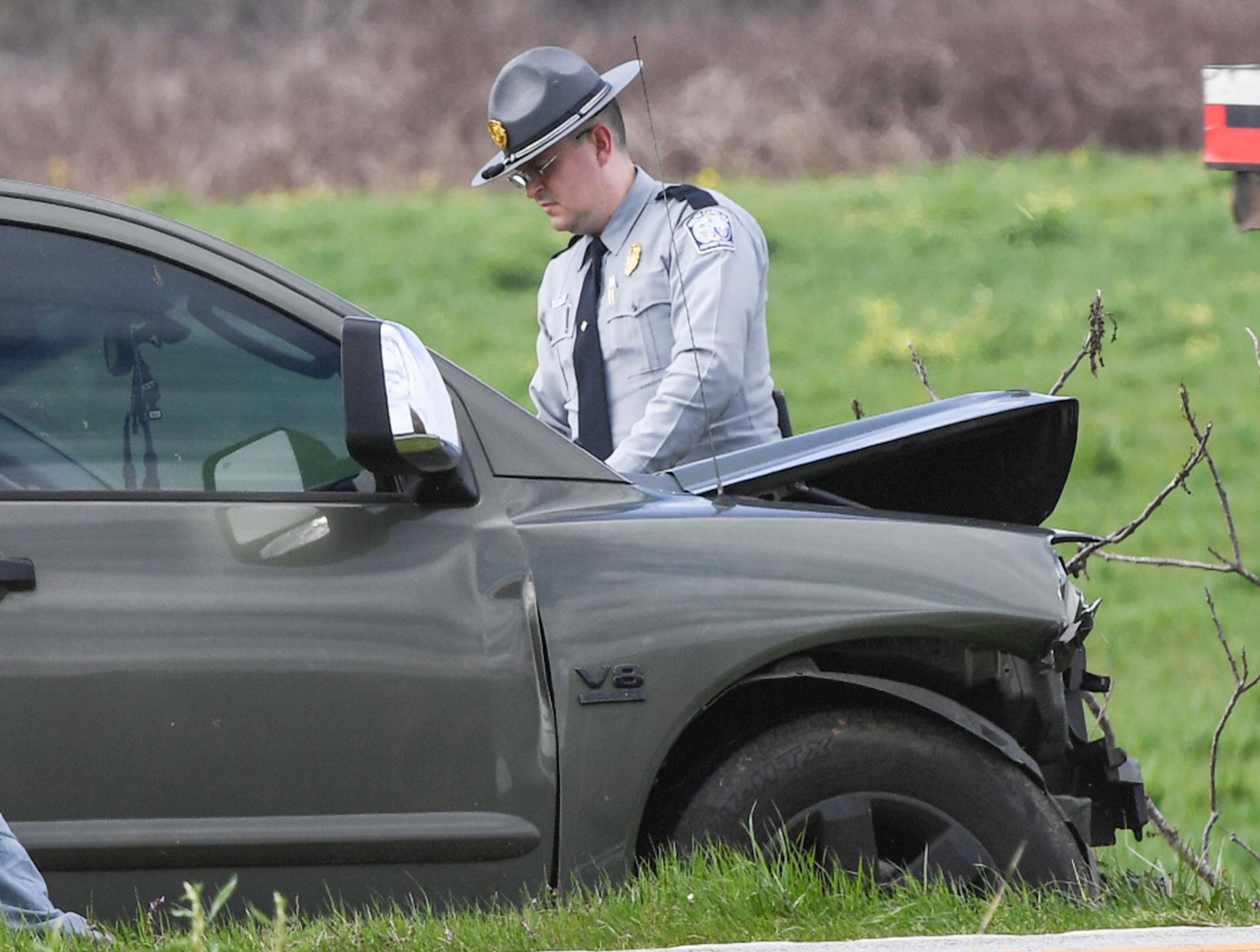 A state trooper gathers information around a pickup truck, involved in an accident with a compact car and a Toyota Camry with Florida license tags on state highway 24 just below Townville in front of Oakdale Baptist Church Tuesday.
