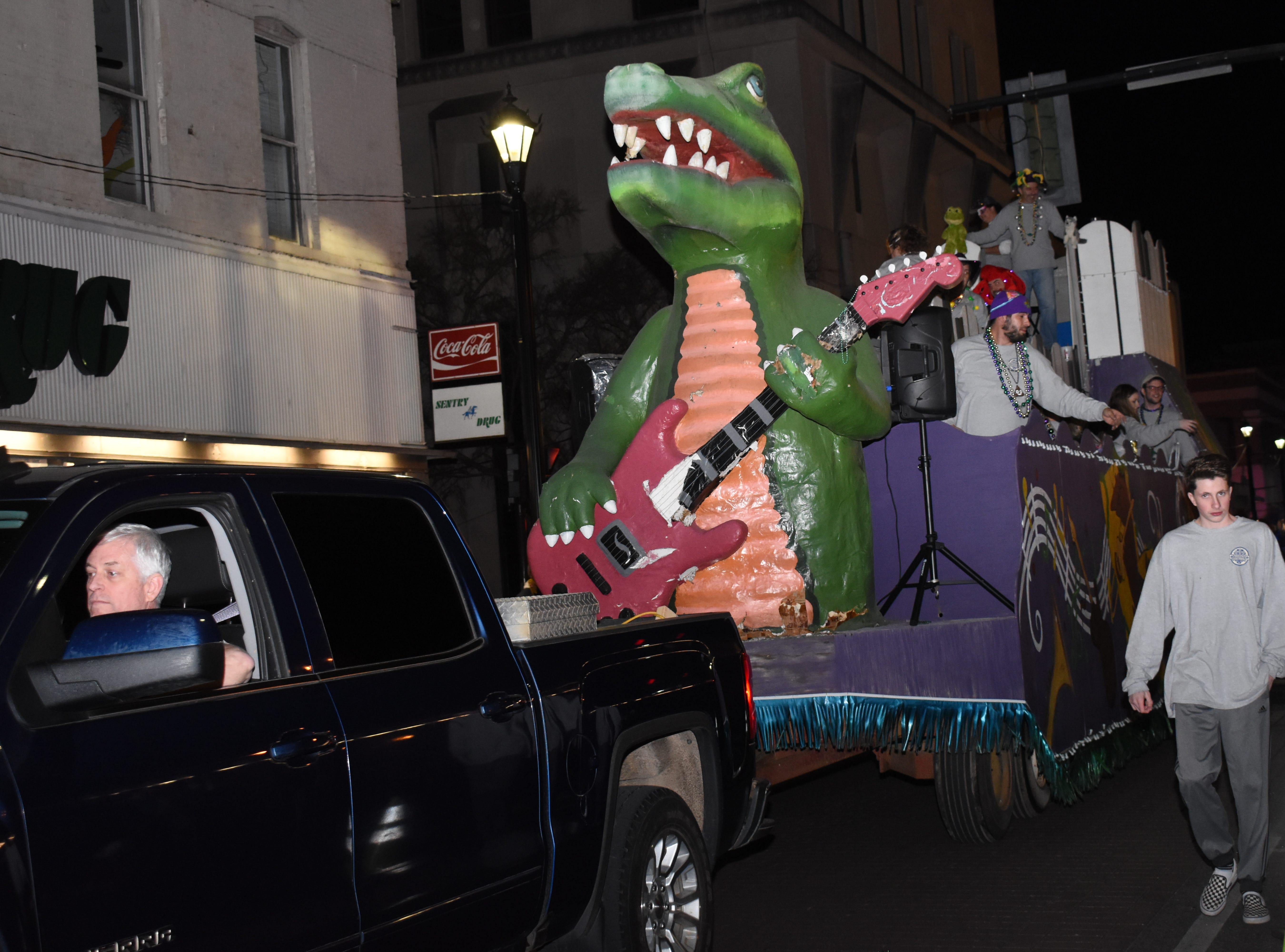 Ethan Coffey walks along the Krewe of Bon Temps float as it passes down Third Street in downtown Alexandria during Pineville's  2019 Light the Night Parade held Monday, Feb. 25, 2019. The parade started in Pineville near Louisiana College and ended in downtown Alexandria. The parade was postponed last Friday due to weather.