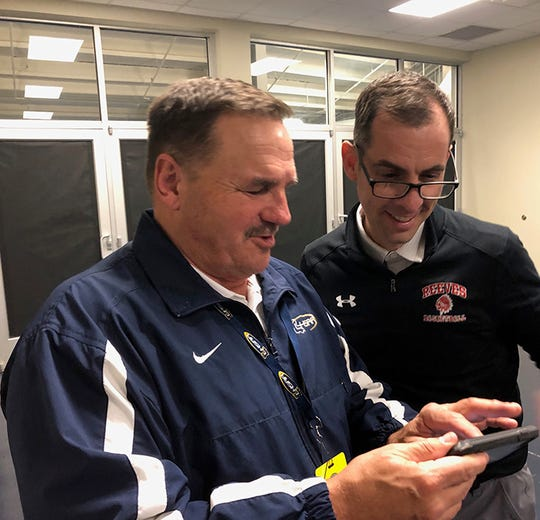 Mitch Small, director of marketing for the Louisiana High School Athletic Association, shows a photo to Reeves girls basketball coach Mark Dronet, Monday night at the Rapides Parish Coliseum. Small is retiring in August after 28 years of service.