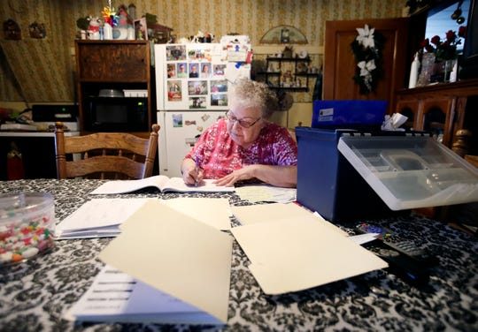 Mary Rieckmann documents farm expenses at her kitchen table while her husband, John, and sons do daily chores around their dairy farm Wednesday Feb. 13, 2019, in Fremont, Wis.